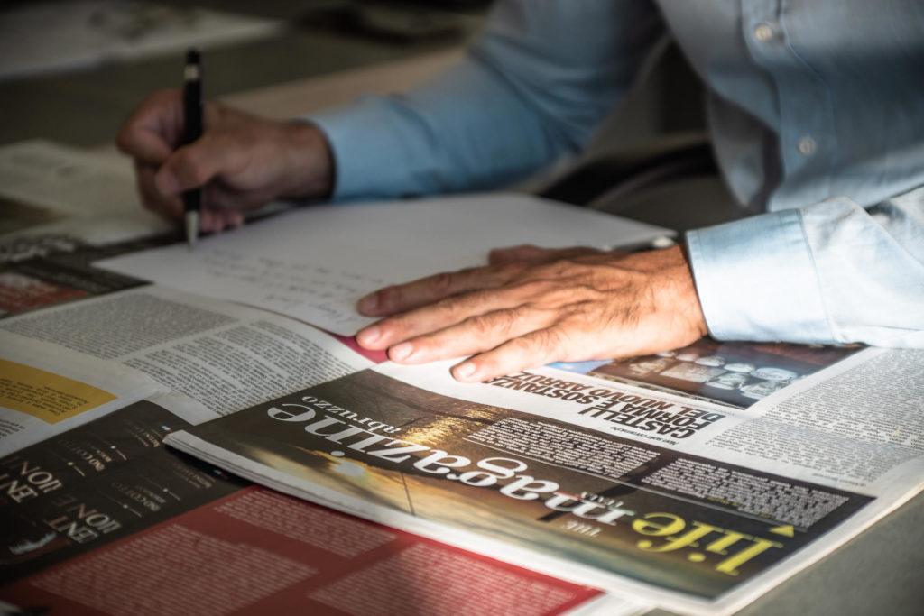 Particolare delle mani di Marco Iaconetti mentre scrive degli appunti alla scrivania sulla quale sono poggiate delle riviste